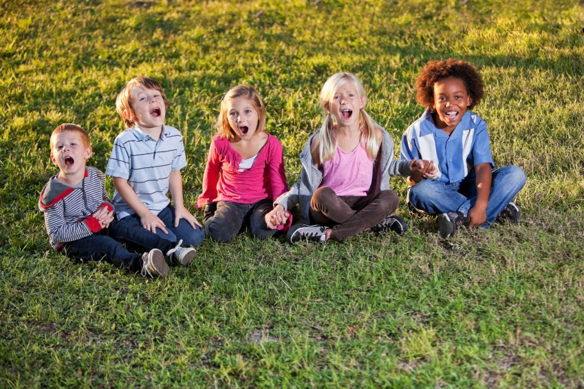 Group of children sitting on grass shouting